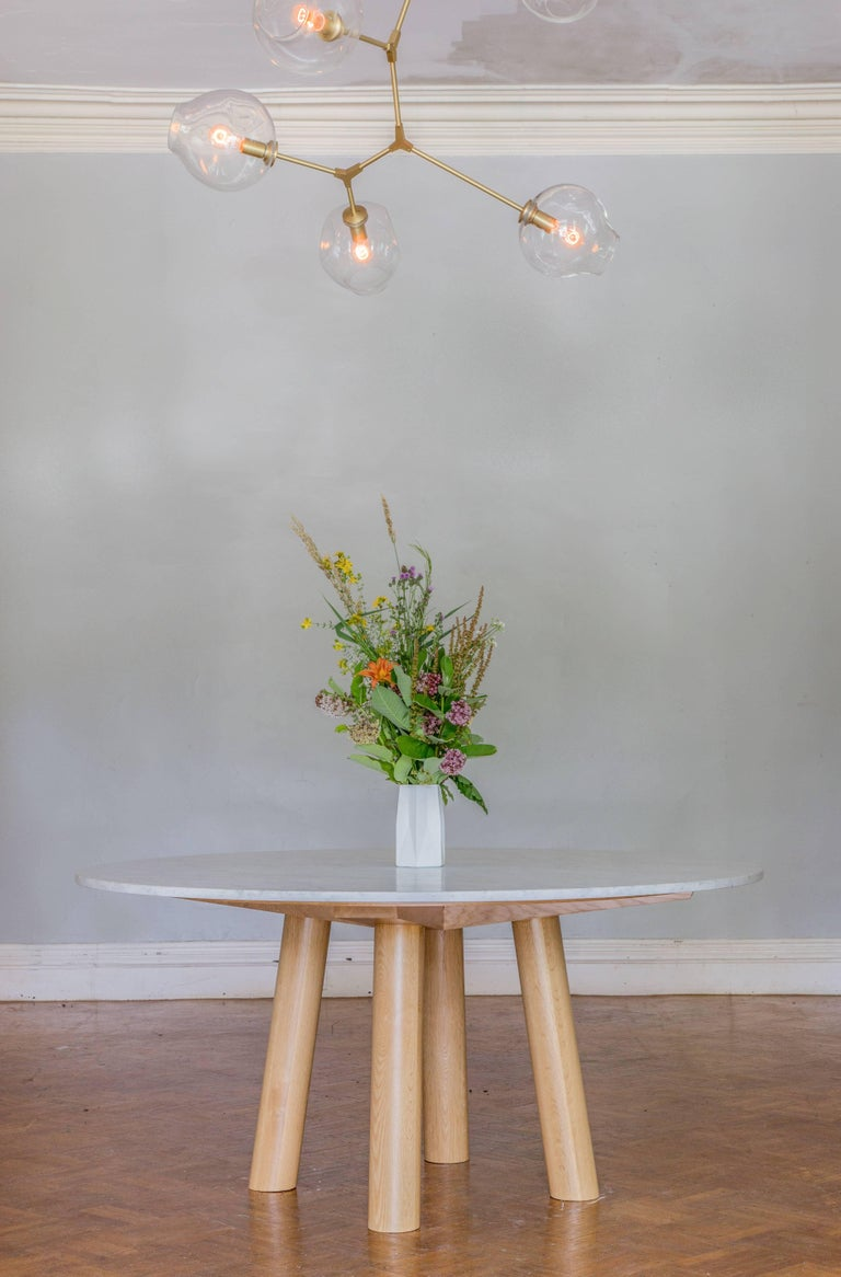 This contemporary, minimal dining table features large diameter round legs and bold trestle supports to give rise to a stone or hardwood top. The table top features a wood surface detail that centers the top to the base and communicates the