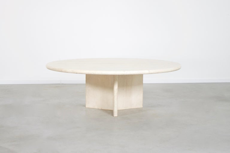 Round travertine coffee table in very good condition.   The table has a round travertine top.   The base is formed of three slabs of travertine, which combine into a triangle or star shape.    The travertine surface is absolutely breathtaking
