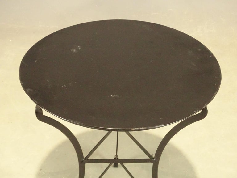 A fine vintage café or bistro table featuring a round or circular metal top, attached to a tripod base.