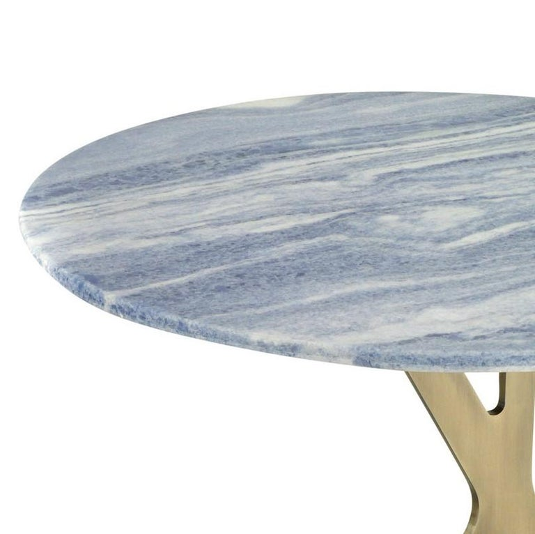 Displaying a unique Silhouette and elegant materials, this large coffee table will splendidly adorn a contemporary interior, while also being a practical display surface. Its asymmetrical structure is made of metal with a satin brass finish and a