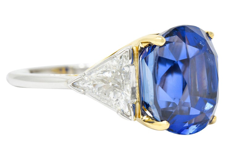 Centering an oval brilliant cut Ceylon sapphire weighing 20.06 carats  Deeply royal blue in color with no indications of heat - Sri Lankan in origin  Basket set in 18 karat gold and flanked by two trillion cut diamonds - V prong set in