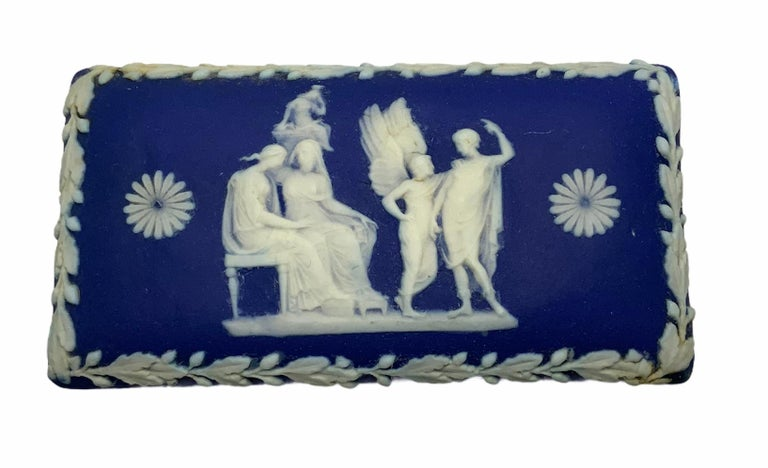 This is a rectangular jasperware trinket box depicting a scene with a white relief technique of two Greek or Roman ladies sitting in a settee while another lady is over them in heaven. In the same scene, an angel appears in front of them talking