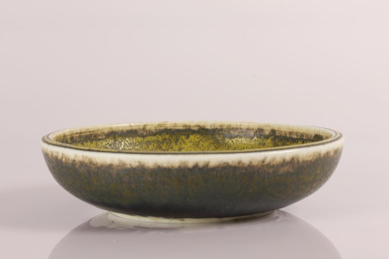 Minor round stoneware bowl model no. 5128 designed by Danish ceramist Knud Halier and manufactured by Royal Copenhagen, early 20th century  The bowl is decorated with Solfatara glaze and the inside of the bowl has got a spiral pattern. It's