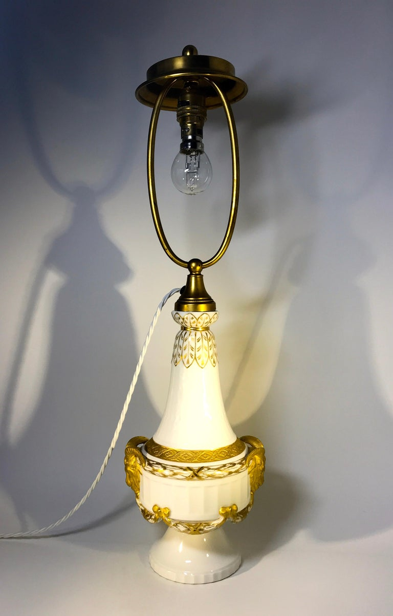 Fabulous Royal Copenhagen XVI style, white porcelain table lamp dated between 1889-1922, in superb condition Sumptuously decorated with gilded swags, rams heads and bows Dated 1889-1922 Signed and Numbered 11537 Measures: Height 22.5 inch,