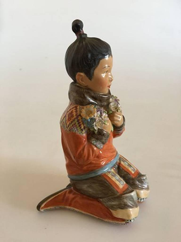 Royal Copenhagen over-glaze figurine Greenland girl #12415. Measures: 15cm and is in good condition, but has chip on flower. Designed by Carl Martin-Hansen.