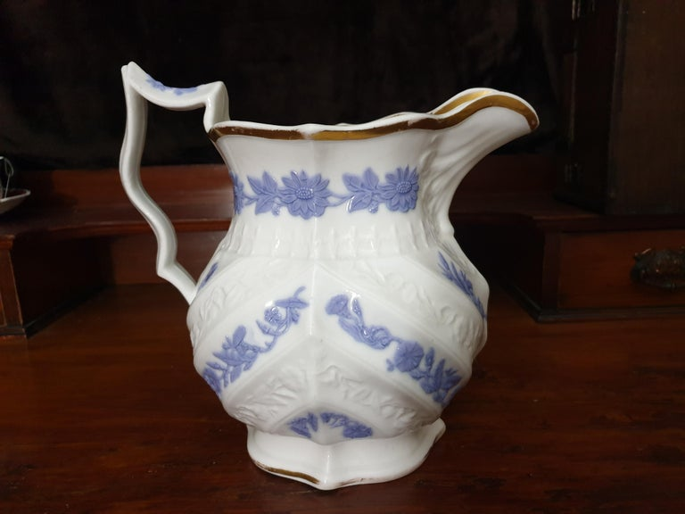 A large Royal Copenhagen water jug, glazed finished with violet embossed sun flowers and flowers finished in 24-karat gold gilt with white embossed flowers. Minor loss of gilding.