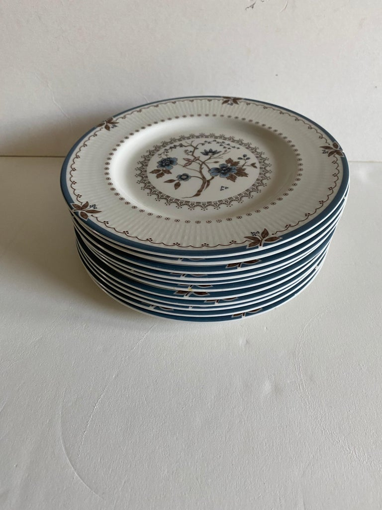 A set of 12 salad and bread plates by Royal Doulton in the Old Colony pattern.  Includes 6 salad plates and 6 bread plates.  Size: Salad plates, 8 inches wide; bread plates 6-1/8 inches wide.