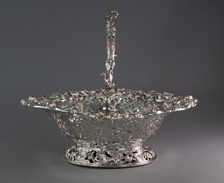 A very large George II silver swing handle harvest basket by William Tuite. Of pierced oval form, adorned with an immaculately cast rim decorated with scrolls, wheat sheaves and grapes surrounding four putti collecting the harvest. Each of the eight