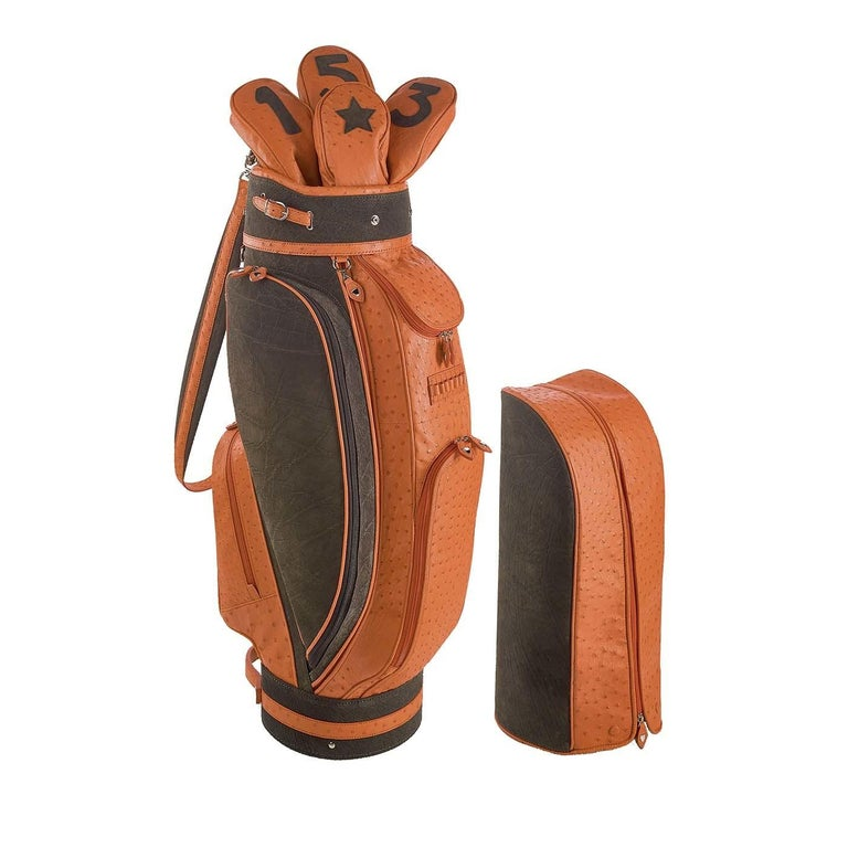 A superb addition to a sunny day spent on the course, this golf bag is part of the Royal collection. It was entirely handmade using fine ostrich leather in a warm orange color with inserts in brown calfskin and metal hardware covered in