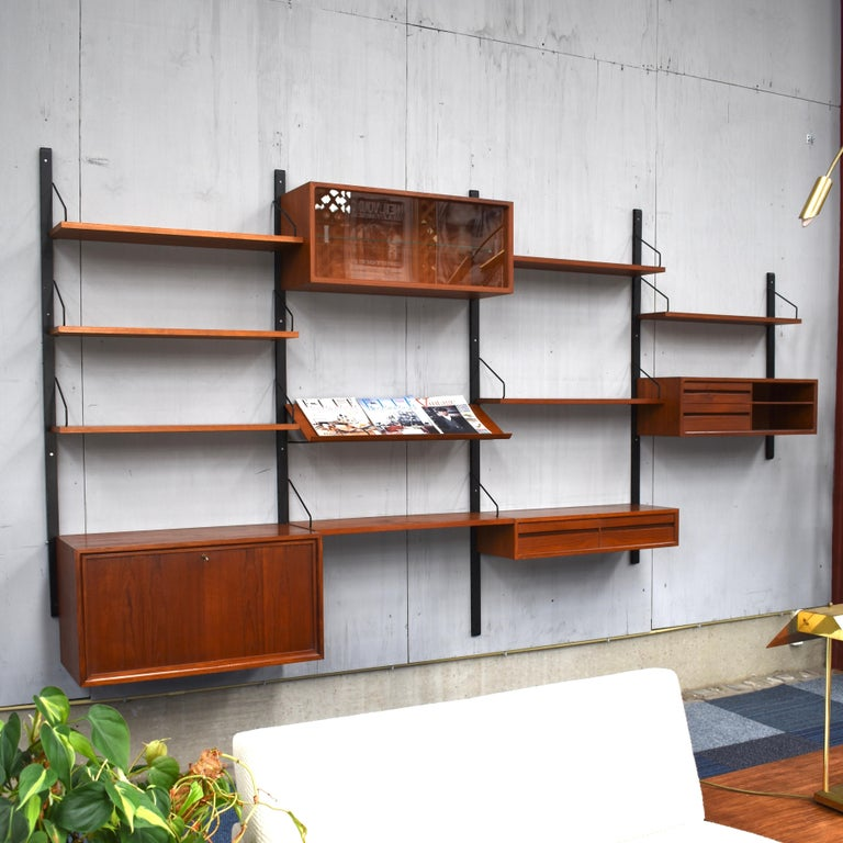 Beautiful Royal series wall unit by Poul Cadovius with much wanted angled lecture shelve. In a beautiful warm wood color and in good condition. The system is modular so it can be arranged to your own liking or expanded with extra units.  This unit