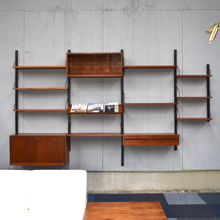 Beautiful Royal series wall unit by Poul Cadovius with much wanted angled lecture shelve. In a beautiful warm wood color and in good condition. The system is modular so it can be arranged to your own liking or expanded with extra units.