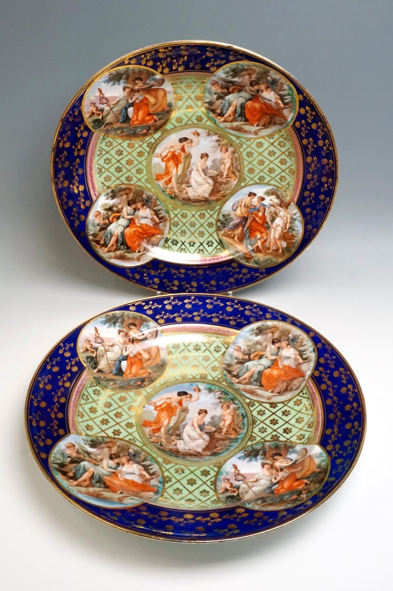 Two large, splendid porcelain plates with elaborate painting: cobalt blue flag with dense, scattered flower painting in gold, delimited by Fine and wider gold rims, collar in pink with a golden bud tendril and subsequent gold rim, mirror with a