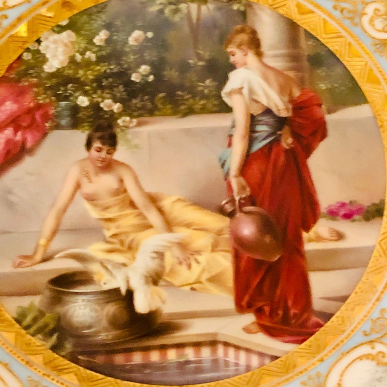 This is a very charming Royal Vienna cabinet plate with a painting of two beautiful ladies and a bird next to a tiled watering hole. One lady is lounging next to her tiled watering hole while her lady in waiting is pouring water for the bird to