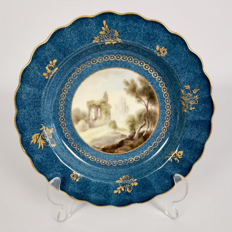 This is a very fine dessert service made by Royal Worcester in the year 1912. It has a powder blue ground and Chamberlain-style landscapes painted by George B. Johnson. The service consists of 2 oval dishes, 2 square dishes and 10 plates.