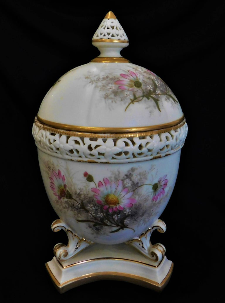 19th century Royal Worcester lidded potpourri porcelain jar, lid and cover, decorated with domed cover and interior lid, surrounded by a pierced border, the body painted with flowers and foliage, on three scrolled feet on trefoil foot.