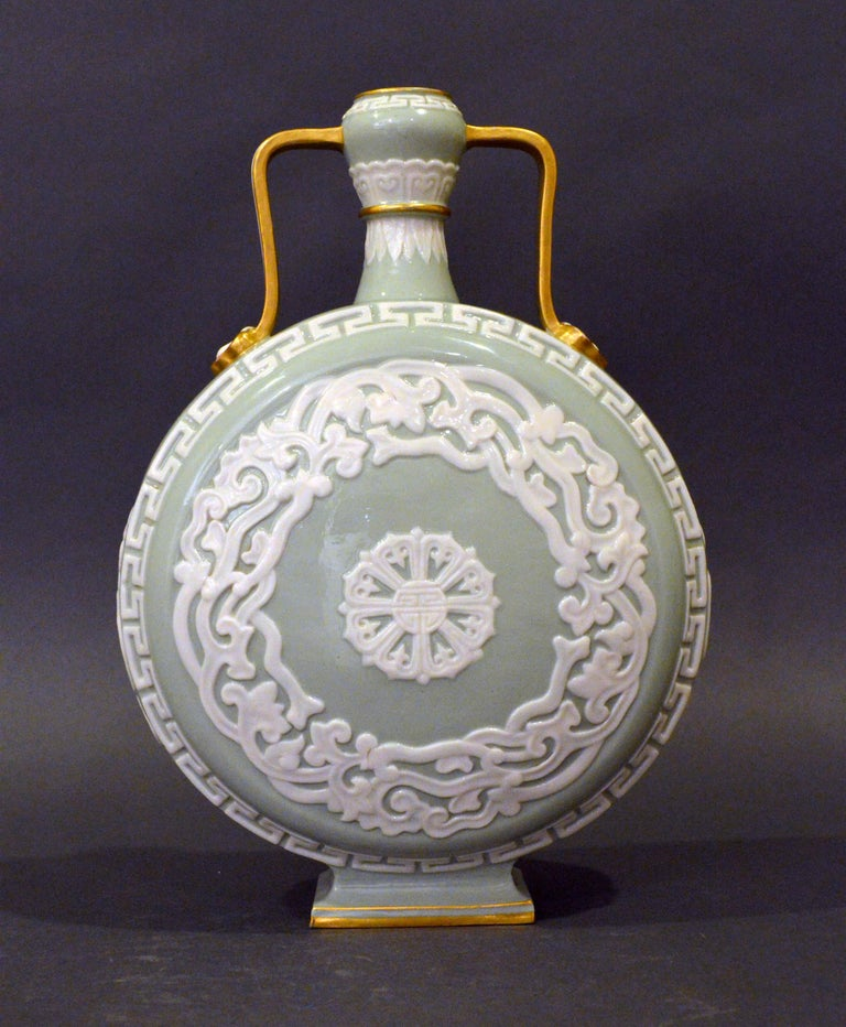 Royal Worcester porcelain moon flask, circa 1880  Elegant Royal Worcester Porcelain chinoiserie aesthetic movement moon flask vase. A refined example of a moon flask vase in celadon green with applied white decoration and gilt covered handles.