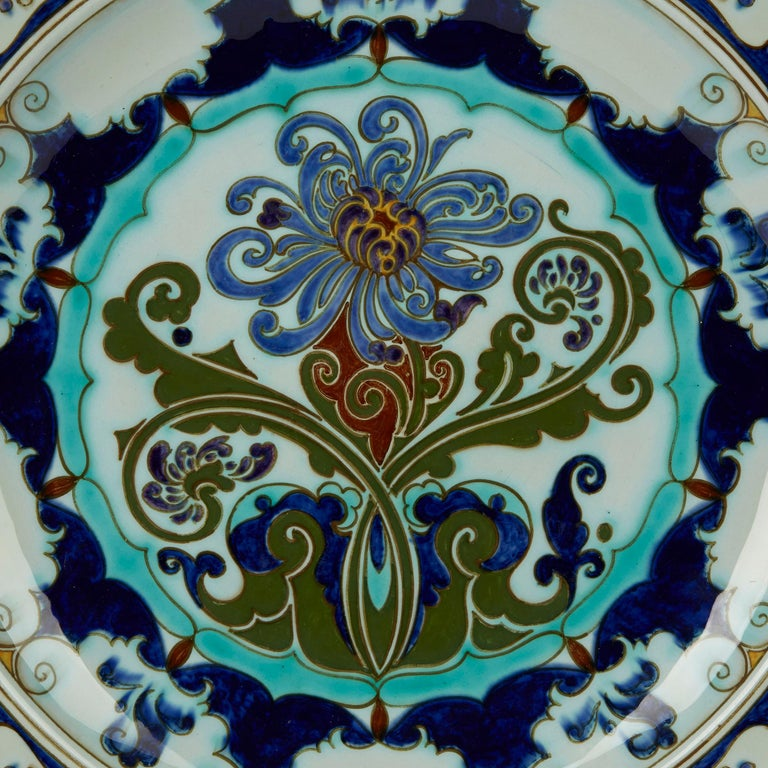 A stunning Dutch Art Nouveau earthenware dish or wall plaque decorated with trailing floral blooms by Rozenburg, Den Haag. This very finely made dish has a slightly raised rim and is hand decorated in colors on a light celadon green ground. With two