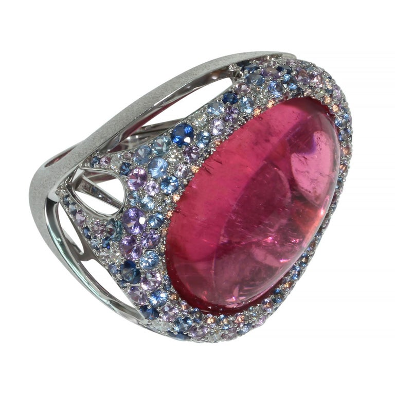 Rubellite 22.86 Carat Diamonds Sapphires 18 Karat White Gold Ring  Combination of Purple and Blue sapphires and Diamonds perfectly highlight the rich pink color of 22.86 Carat Oval Cabochon cut Rubellite. As you can see the Ring is made in an