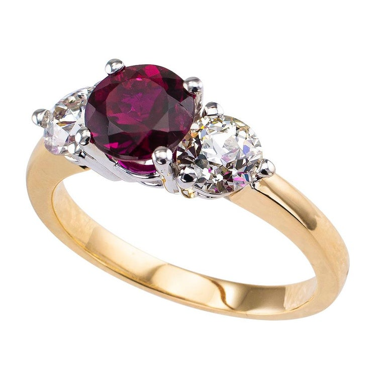 Rubellite and diamond three stone gold ring. Centering upon a round rubellite tourmaline weighing approximately 1.35 carats, flanked by a pair of old European-cut diamonds totaling approximately 1.20 carats, approximately J – L color and VS2 – SI2