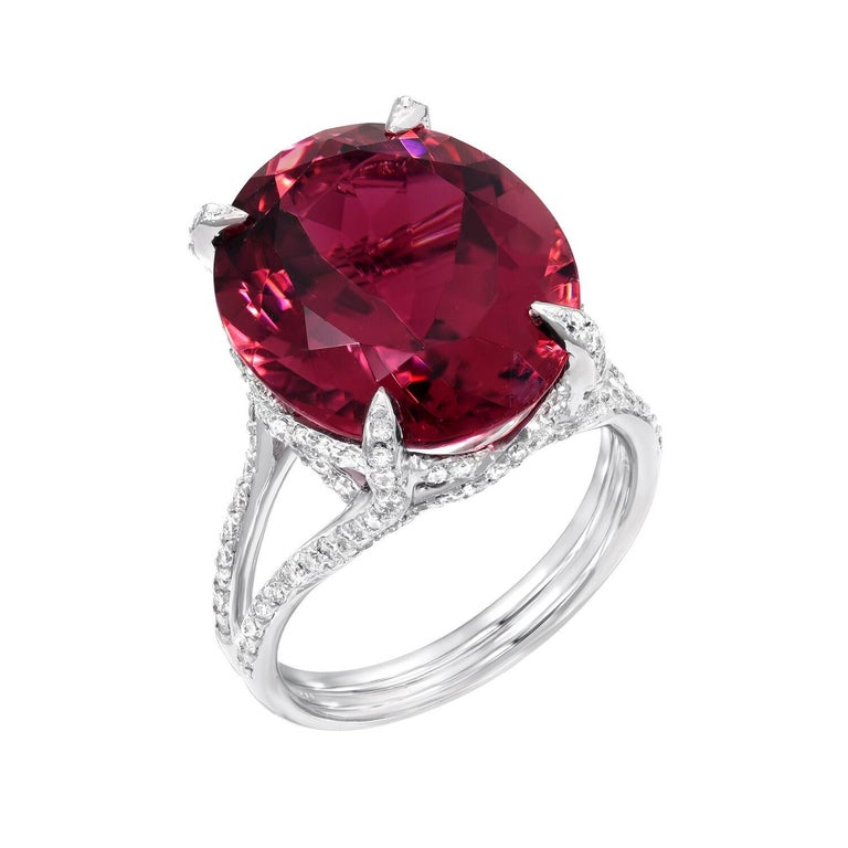 Remarkable Rubelite Tourmaline oval, weighing a total of 11.90 carats, is adorned by a total of 0.88 carats of micro pave diamonds, in this 18K white gold ring. Size 6.5. Resizing is complimentary upon request. Returns are accepted and paid by us