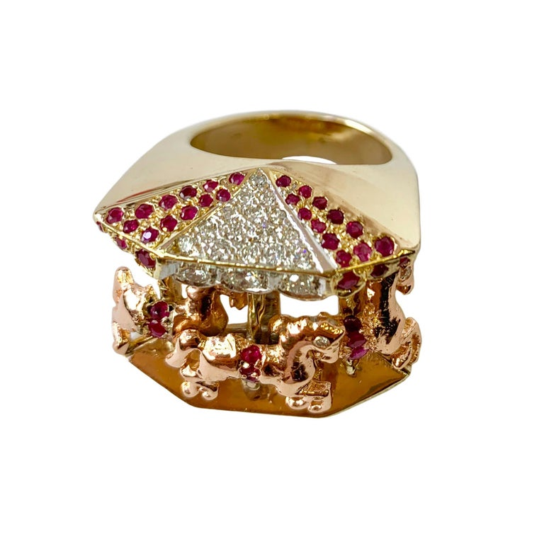 Incredible 14K yellow gold carousel ring set with (39) 1-1.5mm bright red rubies and 31 brilliant cut diamonds with a total weights of approximately 1.00cts. Three rose gold horses are beautifully displayed in the center with diamond eyes and ruby