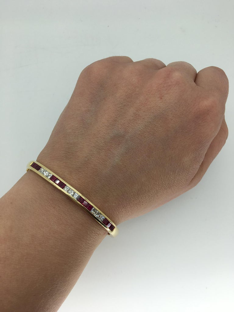 Channel set diamond and ruby bangle bracelet crafted in 18k yellow gold.  Gemstone: Diamond and Ruby Gemstone Weight: 12 Rubies measuring approximately 3mm Diamond Carat Weight: Approximately 1.00CTW Diamond Cut: Princess Cut Diamonds Color: Average