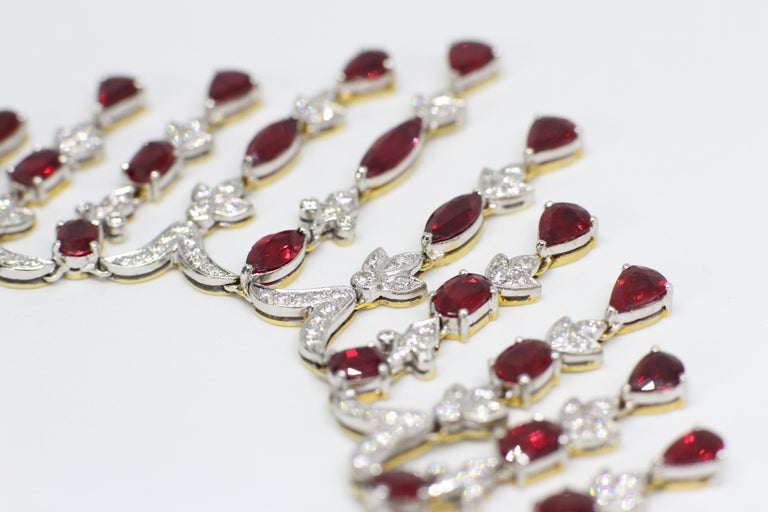 Spectacular ruby and diamond necklace and earring set all in 18 carat white and yellow gold. They are both set with a total of sixty nine rubies - a combination of marquise, pear shaped, round and oval shaped rubies with a minimum approximate total