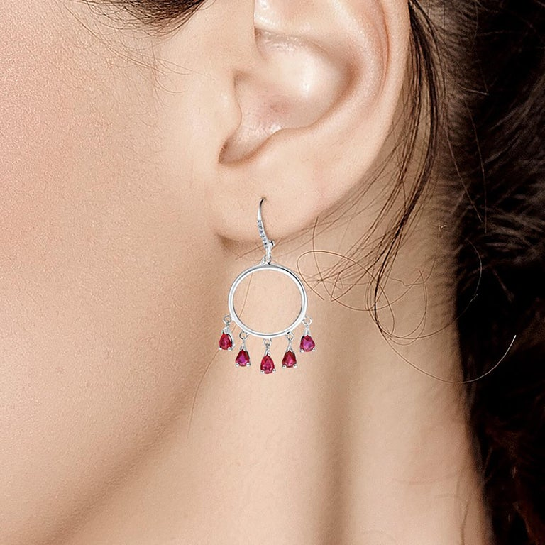 Fourteen karat white gold diamond and ruby circle hoop earrings  Ten pear shape ruby drops weighing 3 carat Diamond weighing 0.20 carat  New Earrings Handmade in USA One of a kind earrings  Our design team select gemstones for their quality,