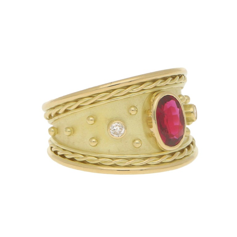 A beautiful diamond and ruby Etruscan inspired dress ring set in solid 18k yellow gold.  The ring is centrally set with a vibrant coloured oval cut red ruby which is rub-over set in a raised setting. To each side of the ruby we see two similarly set