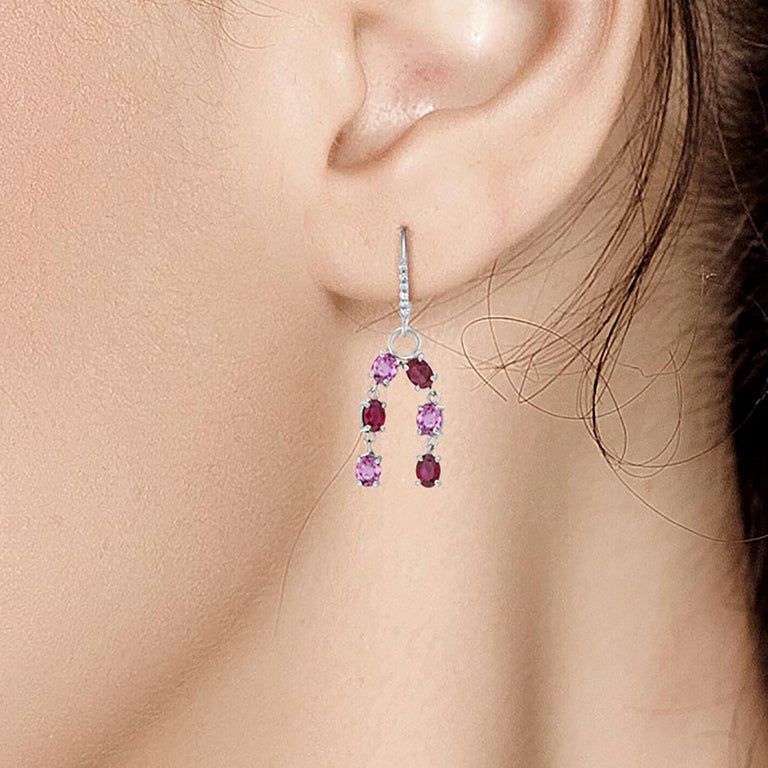 Fourteen karat white gold diamond, ruby, and pink sapphire hoop earrings  Earrings measuring two inches long Six oval shape pink sapphire weighing 2.80 carat Six oval-shaped ruby weighing 2.60 carat Diamond weighing 0.20 carat  One of a kind