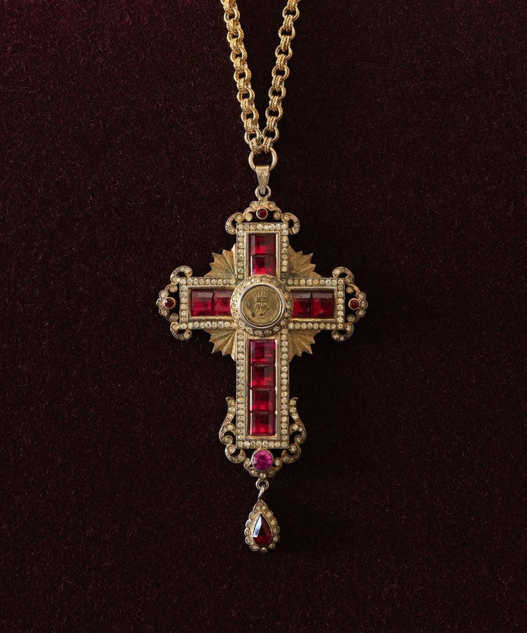 Ruby and diamond cross medallion, Italy, circa 1940.  Comes fitted within original felt-lined, leather-bound box; gilded metal with costume ruby and diamond inlay, with embossed trinity symbol at the center, and hanging from a weighty golden