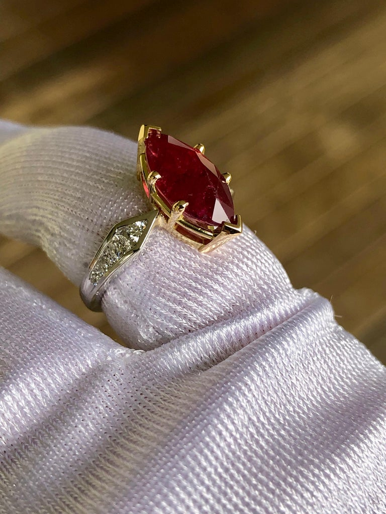 This stunning estate engagement ring stars a natural Mozambique deep, rich red ruby Marquise cut weighing approx. 3.50 carats flanked by brilliant-cut diamonds weighing over 0.40 carat (F color, VS1 clarity). This elegant ring is crafted in a