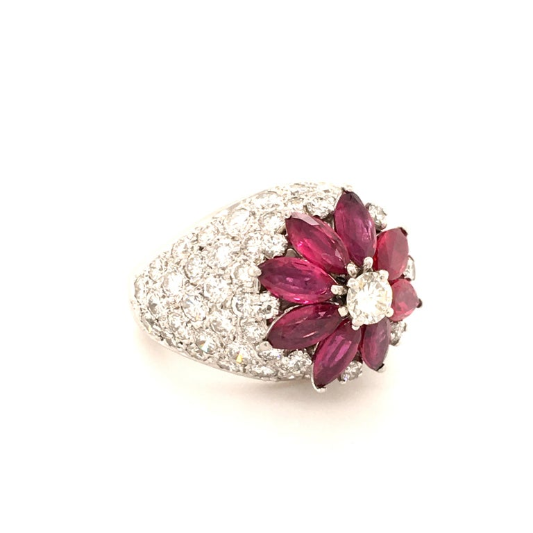 A beautiful platinum ring featuring 8 vivid red marquise shaped rubies, total weight approximately 2.80 carats. Surrounded by 73 brilliant-cut diamonds of G and H color and vs clarity, total weight approximately 3.27 carats.  Size: 51 / US 6