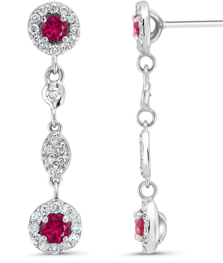 Fourteen karat white gold halo diamond and ruby earrings measuring 1