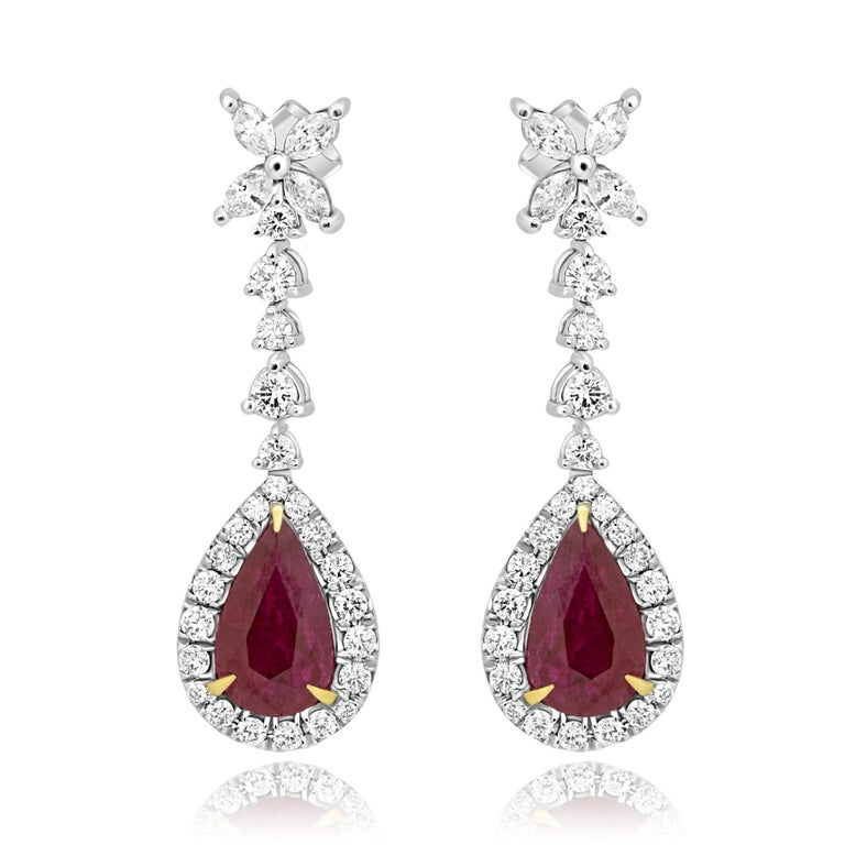 Stunning 2 Pear Shape Ruby 5.29 Carat encircled in a single Halo of white round diamonds 1.26 Carat with 8 White Marquise Diamond on top 0.68 Carat in 18K White Gold Earring.  MADE IN USA 2 Ruby Pear Weight 5.29 Carat Total Stones Weight 7.23 Carat