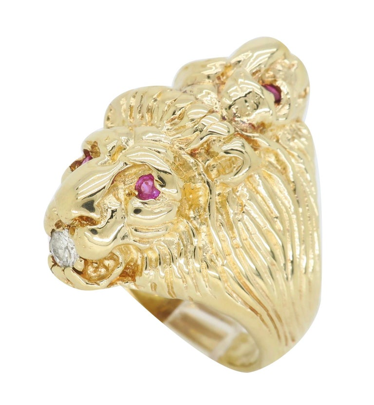 Unique vintage double headed lion ring with diamonds and rubies crafted in 14k yellow gold.  Gemstone: Diamonds and Rubies Gemstone Carat Weight: 4 Approximately 2mm Rubies  Diamond Cut: 2 Round Brilliant Cut  Average Diamond Color: G-I Average