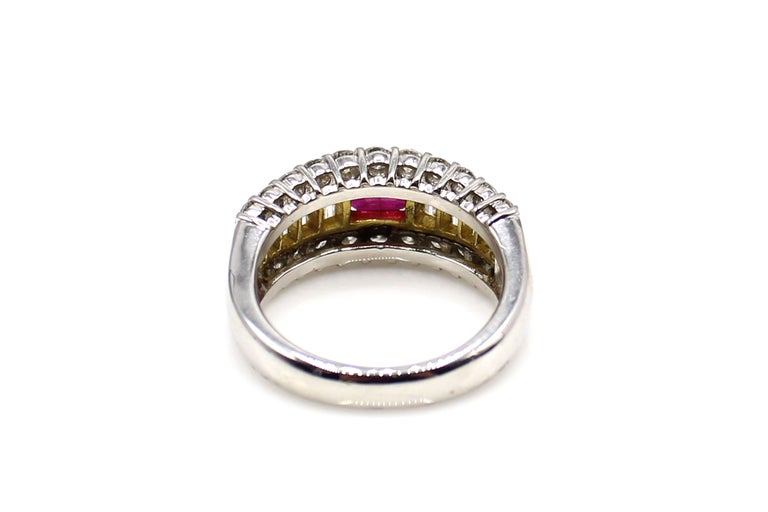 Beautifully designed and masterfully hand-crafted this ring features a centrally set square emerald cut deep red lively ruby securely held in between 2 bars of high polished 18 karat yellow gold. The ruby is embellished by 22 bright white and