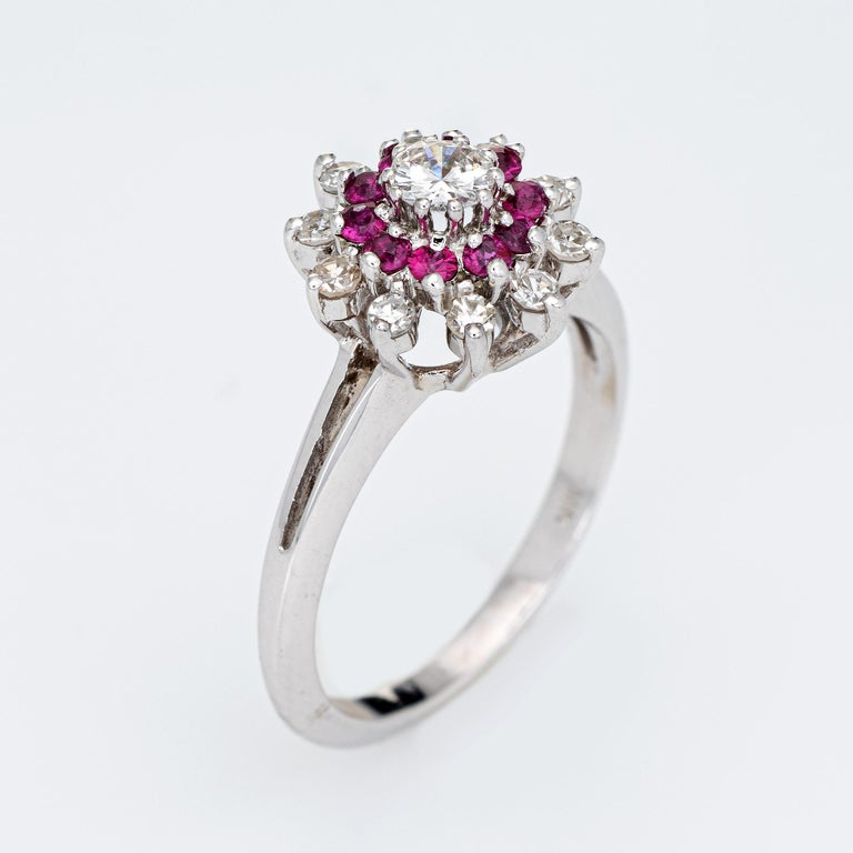 Stylish ruby & diamond ring crafted in 14k white gold.   Center set round brilliant cut diamond is estimated at 0.20 carats. 10 single cut diamonds are estimated at 0.03 carats each. The total diamond weigh is estimated at 0.50 carats (estimated at