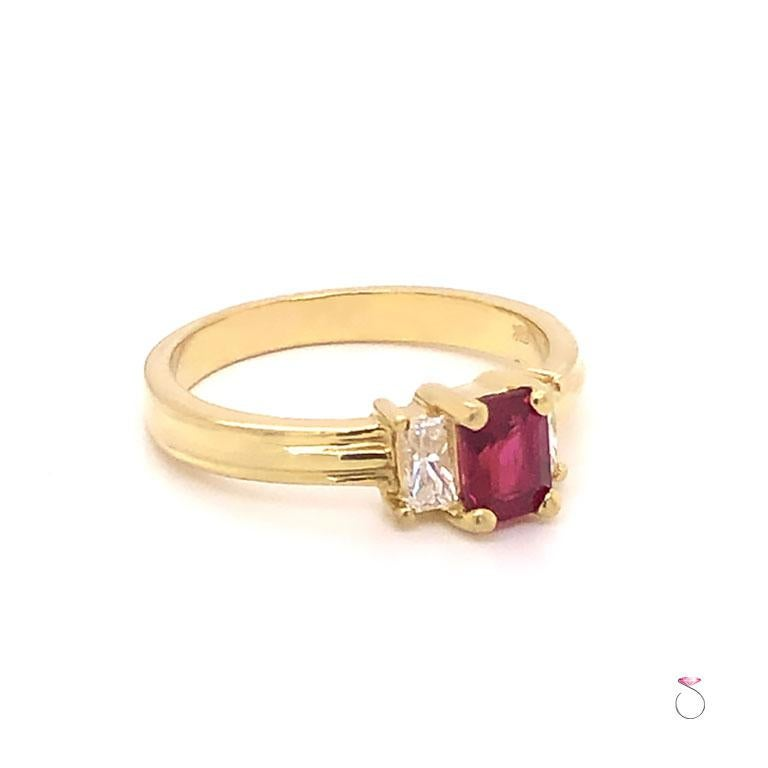 Pretty Ruby & diamond three stone ring in 18K yellow gold. This ring features a stunning Emerald cut Red Ruby in the center, flanked by two radiant cut diamonds, one on each side. The ruby and the diamonds are each set in four prongs. This gorgeous