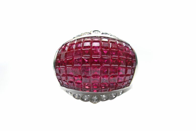 Stunning 18 karat white gold bombe ring centrally invisibly set with 99 square cut intense red rubies. Each of the rubies was perfectly cut and matches so when they were set with this technique, no metal would be showing to the eye. This creates a