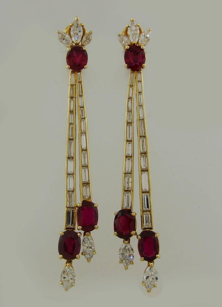 Stunning elegant earrings. The earrings are made of 18 karat (stamped) yellow gold, oval faceted ruby and marquise and baguette cut diamonds. Diamond total weight  approximately 4.38 carats, ruby total weight approximately 10.36 carats. They measure