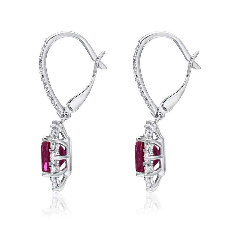 Ruby earrings showcasing a magnificent pair of cushion cut Rubies weighing a total of 2.84 carats, adorned by a total of 1.28 carats of round brilliant diamonds, in 18K white gold lever back earrings. The C. Dinaigre certificate is attached to the
