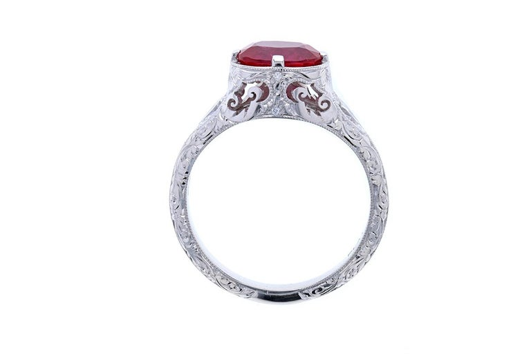 An Edwardian style engagement ring with an exquisite combination of an oval ruby, pear shaped diamonds and engraving make this ring a thing of unique beauty with a jaw dropping center stone. This stunning ring is crafted in Platinum and contains an