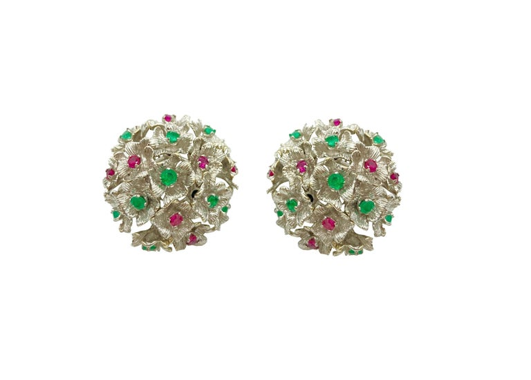 A beautiful pair of white gold earrings featuring en tremblant flowers embellished with brilliant cut rubies and emeralds. Circa 1960.