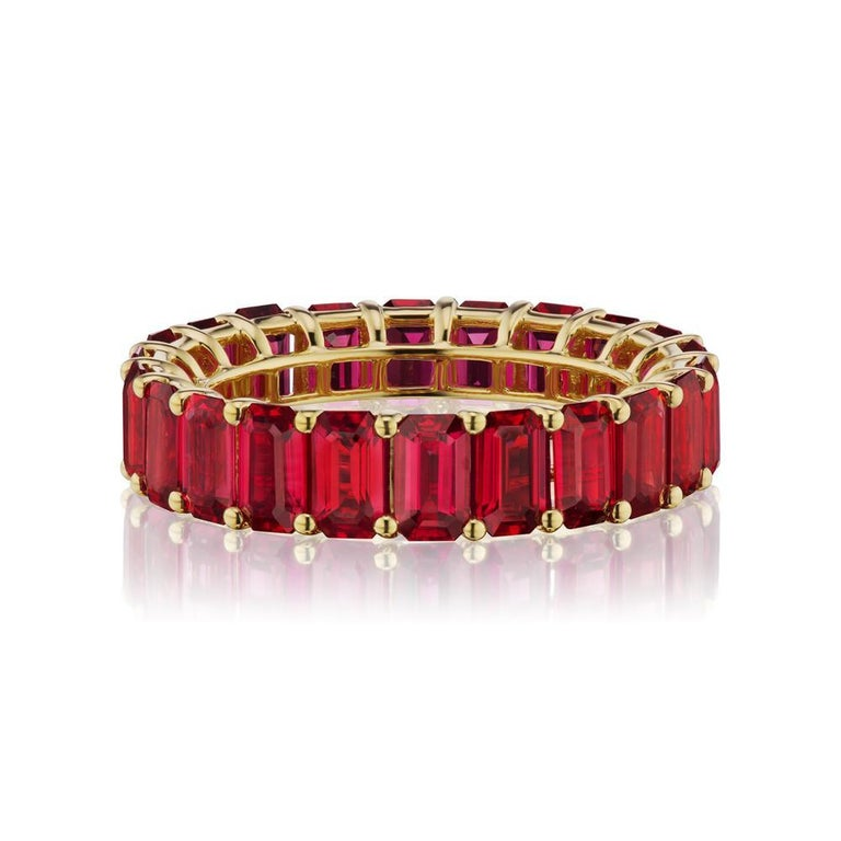 PIGEON BLOOD COLOR RUBY ETERNITY BAND A timeless eternity Ruby band in 18k Yellow Gold with emerald-cut stones around. This design is one for the classics. ( Ring Size 7 ) Item:# 03793 Setting:18K Y Color Weight:7.23 ct. of Ruby