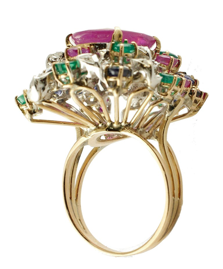 Charming fashion ring, mounted in 14Kt white gold and 14Kt  gold, with a oval shape ruby in the middle and on top of a cluster of emeralds, blue sapphires and diamonds. Ring Size: ITA 15 - French 55 - US 7 - UK O Tot weight 16.5 gr Diamonds 0.72