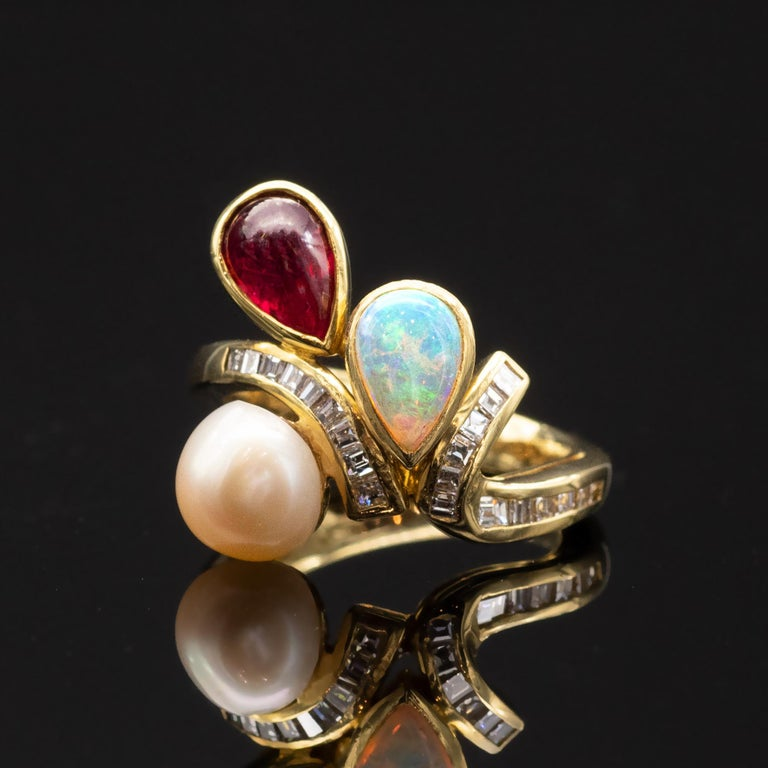 A truly elegant one of a kind Ring, A pear shape opal a cabochon ruby as well as a round pearl  are delicately placed on both sides of a shank. They seem to defy gravity. The shank itself has the graceful stem like movement  is set with 21 square