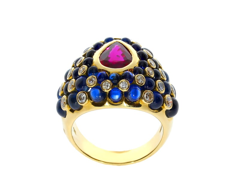 This Chatila 18 carat yellow gold ruby cocktail ring with circular diamond and blue sapphire accents is perfect for any occasion.  Details:  - 32 Diamonds with a total weight of 0.79 carats. - 1 Ruby with a total weight of 1.46 carats. - 38