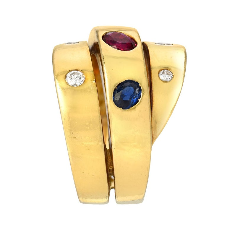 A wrapped design features an oval ruby flanked by oval sapphires on the central element accented with round diamonds totaling approximately 0.15 carat mounted in 18 karat yellow gold, stamped with VCA makers mark, B 5308 63. Size/Dimensions: US ring