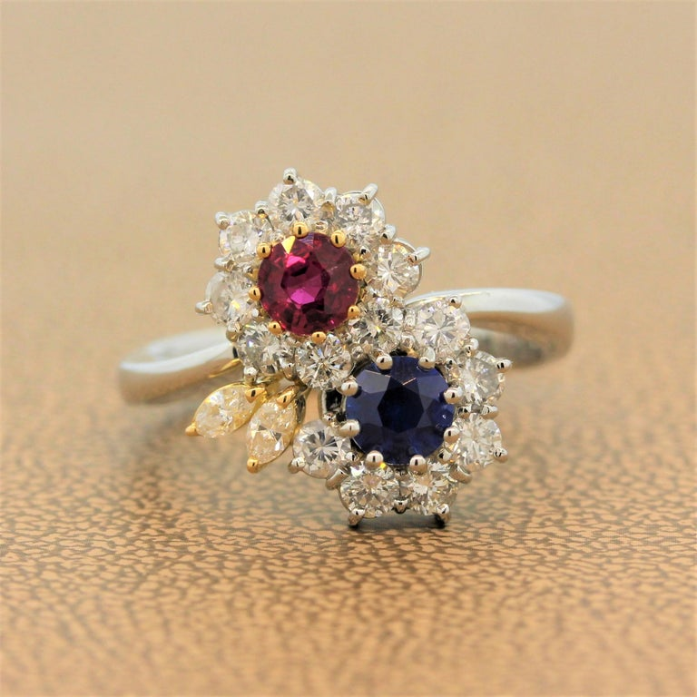 A lovely sweet ring featuring two flowers. One flower has a vivid red ruby center and the other has a royal blue sapphire center weighing a total of 1.24 carats. The precious gemstones are accented by 0.85 carats of round cut diamonds in a platinum